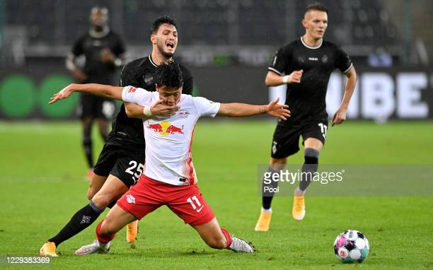 Moenchengladbach's Ramy Bensebaini in action with Leipzig's Hee-chan Hwang during the Bundesliga match between Borussia Moenchengladbach and RB...
