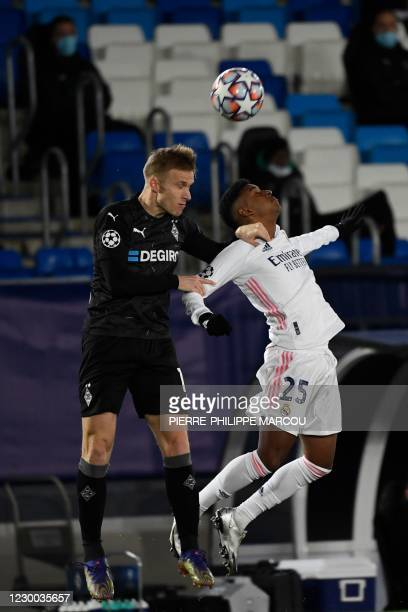 Moenchengladbach's Swedish defender Oscar Wendt and Real Madrid's Brazilian forward Rodrygo jump for the ball during the UEFA Champions League group...