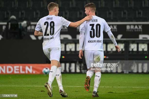 Moenchengladbach's Swiss defender Nico Elvedi celebrates scoring the opening goal with his teammate Moenchengladbach's German defender Matthias...