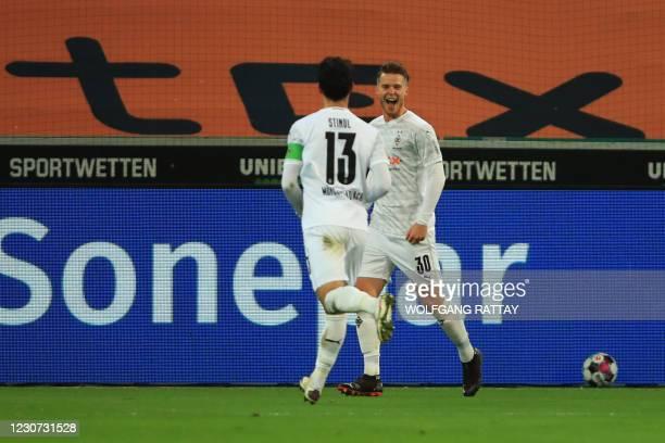 Moenchengladbach's Swiss defender Nico Elvedi celebrates scoring the equalising goal 2:2 with Moenchengladbach's German midfielder Lars Stindl during...