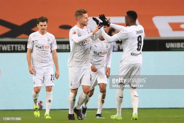 Moenchengladbach's Swiss defender Nico Elvedi celebrates scoring the equalising goal 2:2 with Moenchengladbach's Swiss midfielder Denis Zakaria...