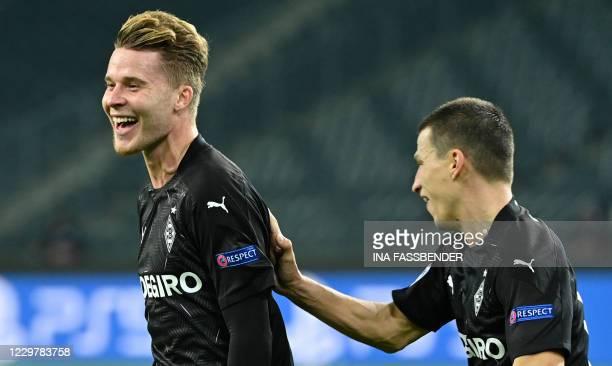 Moenchengladbach's Swiss defender Nico Elvedi celebrates with Moenchengladbach's Austrian defender Stefan Lainer after scoring the 20 during the UEFA...