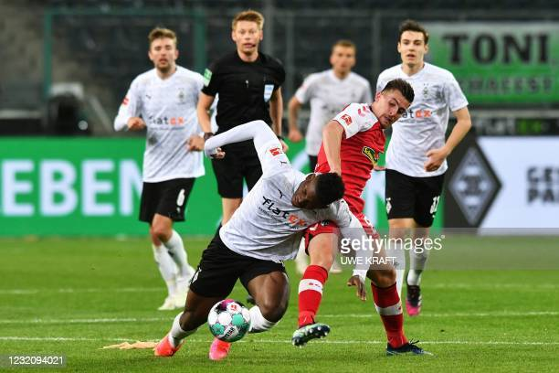 Moenchengladbach's Swiss forward Breel Embolo and Freiburg's French midfielder Baptiste Santamaria vie for the ball during the German first division...