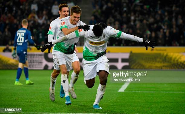 TOPSHOT Moenchengladbach's Swiss forward Breel Embolo celebrates with German forward Patrick Herrmann after scoring a goal during the German first...