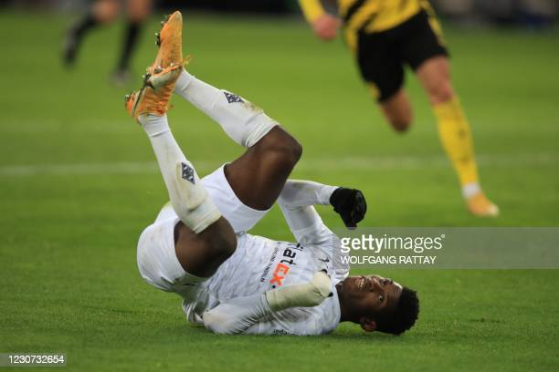 Moenchengladbach's Swiss forward Breel Embolo lies on the ground during the German first division Bundesliga football match Borussia Moenchengladbach...