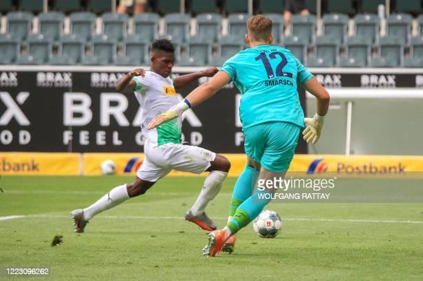 Moenchengladbach's Swiss forward Breel Embolo scores his team's second goal past Hertha Berlin's German goalkeeper Dennis Smarsch during the German...