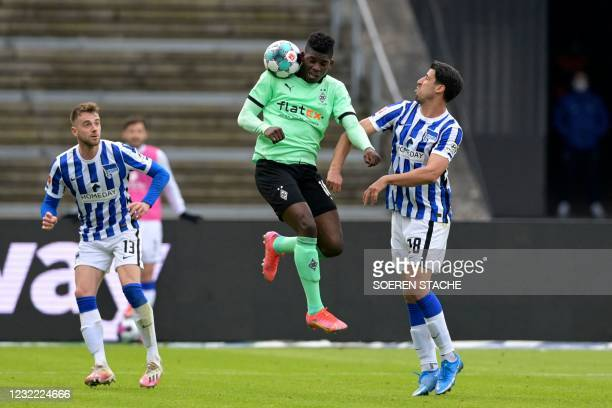 Moenchengladbach's Swiss forward Breel Embolo vies for the ball with Hertha Berlin's German midfielder Sami Khedira and Hertha Berlin's German...