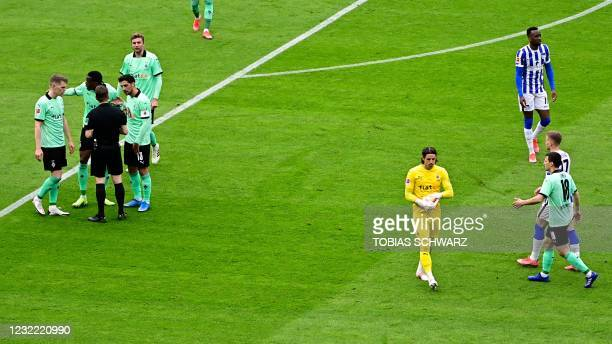 Moenchengladbach's Swiss goalkeeper Yann Sommer leaves the pitch while Moenchengladbach's players speak with the referee after Sommer received a red...