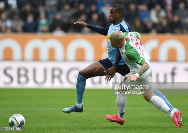 Moenchengladbach's Swiss midfielder Denis Zakaria and Augsburgs midfielder Philipp Max vie for the ball during the German first division Bundesliga...