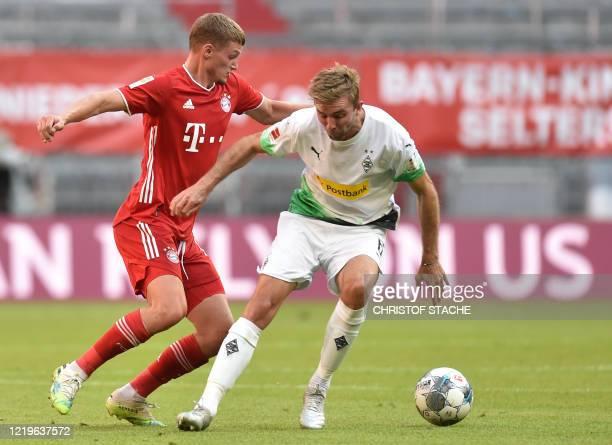 Moenchengladbach's Swiss midfielder Denis Zakaria and Bayern Munich's midfielder Michael Cuisance vie for the ball during the German first division...