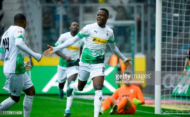 Moenchengladbach's Swiss midfielder Denis Zakaria celebrates with Moenchengladbach's French forward Alassane Plea after scoring the 10 goal during...