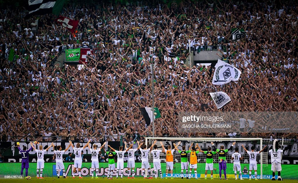 Moenchengladbach's teammates celebrate with the fans after the German first division Bundesliga football match of Borussia Moenchengladbach vs Bayer 04 Leverkusen in Moenchengladbach, western Germany, on August 27, 2016. / AFP / SASCHA