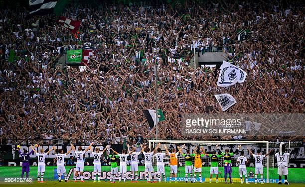 Moenchengladbach's teammates celebrate with the fans after the German first division Bundesliga football match of Borussia Moenchengladbach vs Bayer...