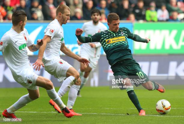 Moenchengladbach's Thorgan Hazard and Augsburg's Jeffrey Gouweleeuw and Ragnar Klavan vie for the ball during the German Bundesliga soccer match...
