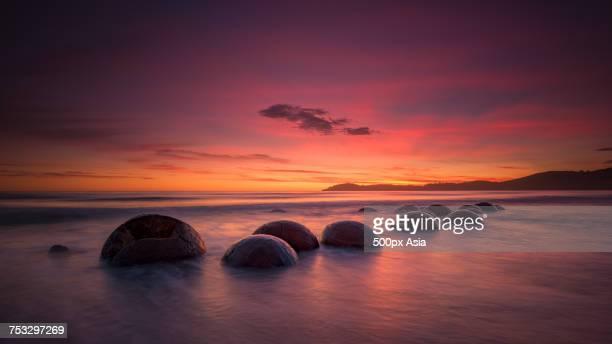 Moeraki Boulders on beach under romantic sky at sunset, Koekohe Beach, New Zealand