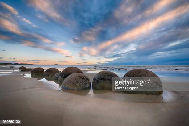 Moeraki Boulders on Koekohe Beach with dramatic sky, Otago coast, South Island of New Zealand. Moeraki, Hampden, Koekohe Beach, Otago Coast, South Island, New Zealand.