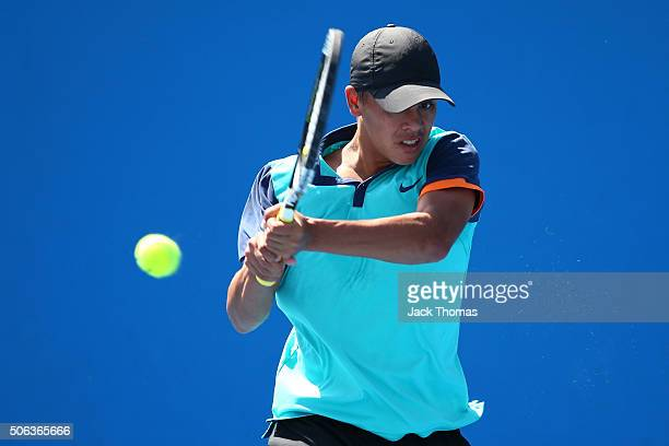 Moerani Bouzige of Australia plays a backhand in his first round juniors match against Nawakarn Khunjan of Thailand during the Australian Open 2016...