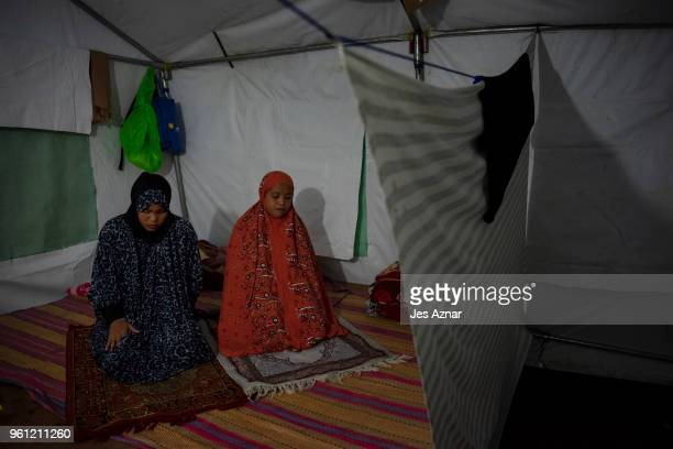 Mofida Pangarungan and Melanie Palala prays the Tarawe inside their shelter as the makeshift mosque for them was not finished in time for the start...
