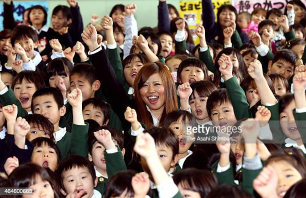 Mogul skiier Arisa Murata, who works for Gyogaku Kindergarten as a teacher, poses for photographs with pupils during the sending-off party on January...