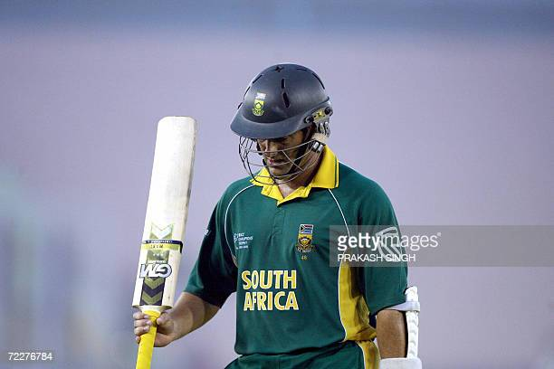 South Africa cricketer Mark Boucher rasies his bat as he walks back to the pavillion after being caught out during the ICC Champions Trophy 2006...