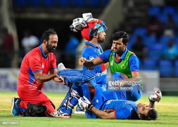 Mohamad Asghar of Afghanistan receives attention from team handler Fa Zal Malik during the 3rd and final T20i match between West Indies and...