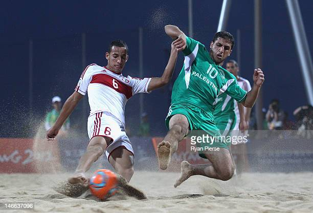 Mohamad Mechleb Matar of Lebanon is tackled by Mohammed Barakat of Palestine during the Beach Soccer Men's Bronze Medal Match between Palestine and...