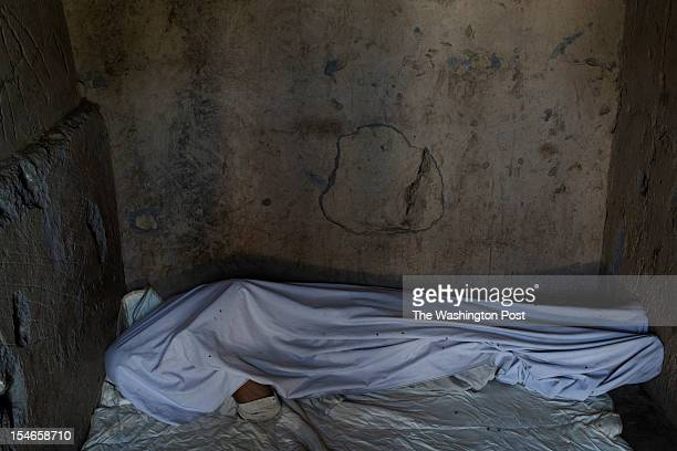 Mohamad Sadik lies chained in a concrete cell of the Mia Ali Sahib shrine outside Jalalabad Afghanistan on October 19 2012 Relatives bring those with...