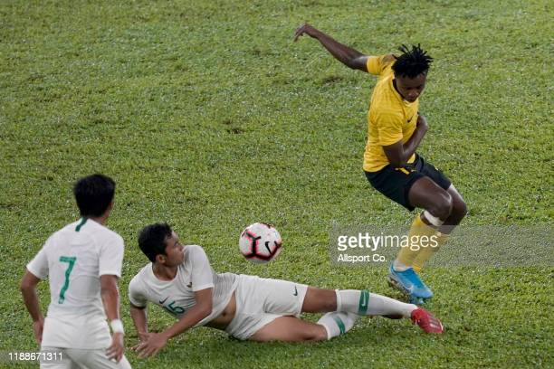 Mohamadou Sumareh of Malaysia battles Rudolof Yanto of Indonesia during the 2022 Qatar FIFA World Cup Asian qualifier group G match between Malaysia...