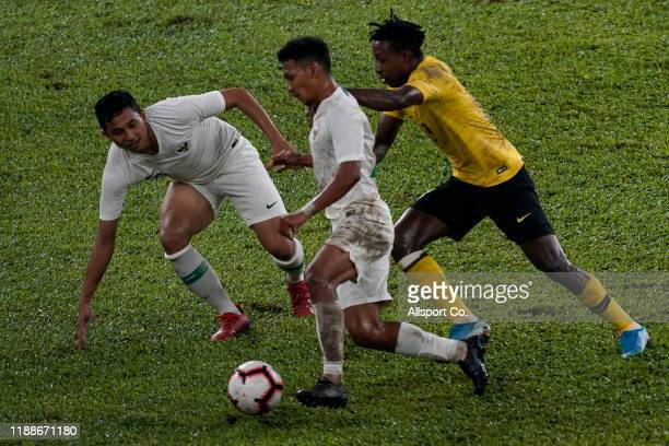 Mohamadou Sumareh of Malaysia battles Teuku Muhammad Ichsan of Indonesia during the 2022 Qatar FIFA World Cup Asian qualifier group G match between...