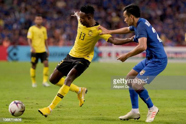 Mohamadou Sumareh of Malaysia holds off Korrakot EriyaUdomsiri of Thailand during the AFF Suzuki Cup semi final second leg match between Thailand and...