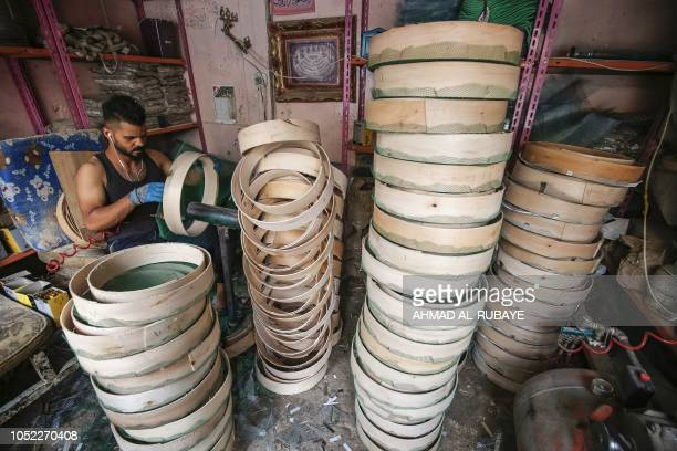 Mohamed a 22yearold Iraqi craftsman manufactures wooden sieves to be used to filter flour for baking or sand for construction in a workshop in the...