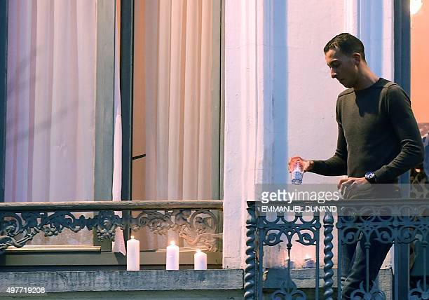Mohamed Abdeslam a brother of two men who helped carry out a series of attacks in Paris last week places candles on a window ledge of the family's...