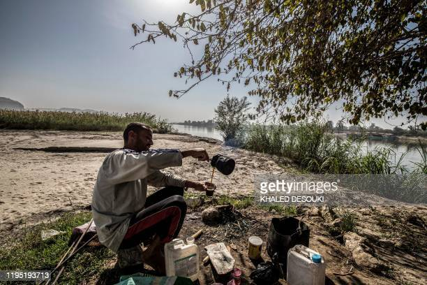 Mohamed Abou Mahmud, a 27-year-old farmer, pours tea as he sits along the bank of the Nile river in the village of Gabal al-Tayr north of Egypt's...