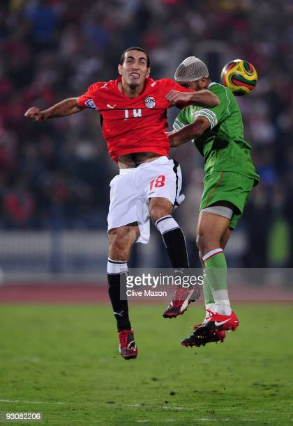 Mohamed Aboutrika of Egypt jumps with Kaled Lemmouchia of Egypt during the FIFA2010 World Cup qualifying match between Egypt and Algeria at the Cairo...