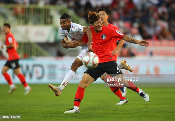 Mohamed Al Romaihi of Bahrain tangles with Kim MinJae of South Korea during the AFC Asian Cup round of 16 match between South Korea and Bahrain at...