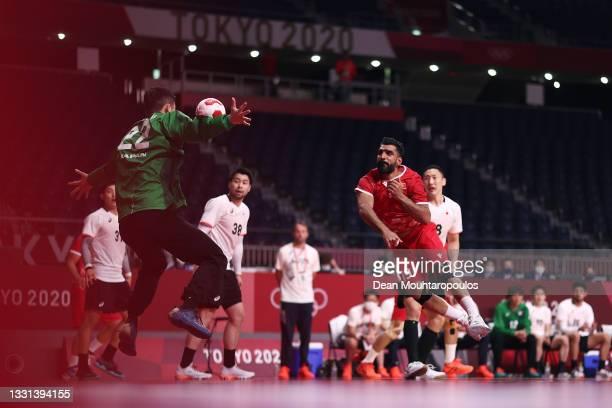 Mohamed Ali of Team Bahrain shoots and scores a goal against Motoki Sakai of Team Japan during the Men's Preliminary Round Group B handball match...