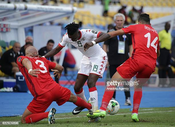 Mohamed Amine Ben Amor and Aymen Abdennour of Tunisia vie with Bertrand Traore of Burkina Faso during the 2017 Africa Cup of Nations quarterfinal...