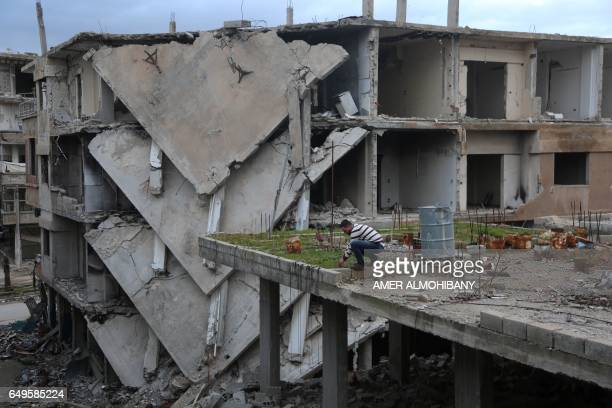 Mohamed Ataya a 31yearold Syrian man known as 'Abu Maher' tends to his plants on the rooftop of his damaged building in the Syrian rebelheld town of...