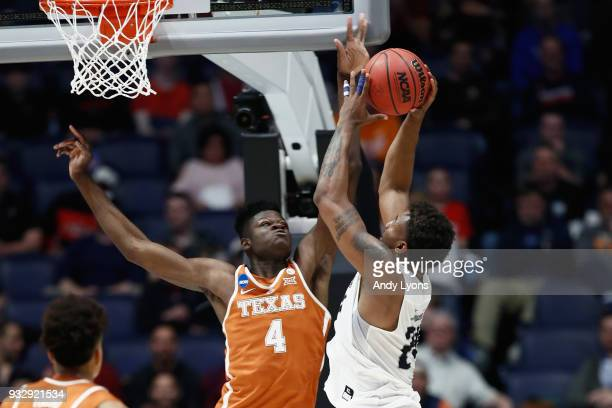 Mohamed Bamba of the Texas Longhorns blocks a shot by Jordan Caroline of the Nevada Wolf Pack during the game in the first round of the 2018 NCAA...