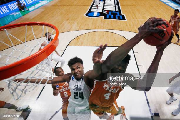 Mohamed Bamba of the Texas Longhorns grabs a rebound from Jordan Caroline of the Nevada Wolf Pack during the game in the first round of the 2018 NCAA...