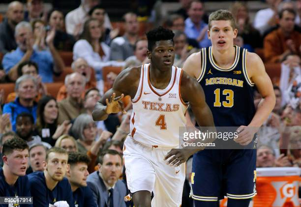 Mohamed Bamba of the Texas Longhorns reacts after sinking a three point shot as Moritz Wagner of the Michigan Wolverines trails him at the Frank...