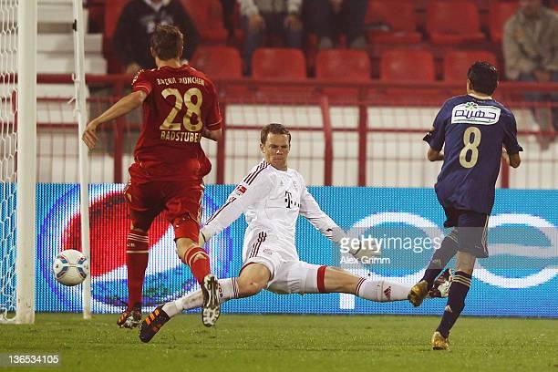 Mohamed Barakat of AlAhly scores his team's first goal against goalkeeper Manuel Neuer and Holger Badstuber of Muenchen during the international...