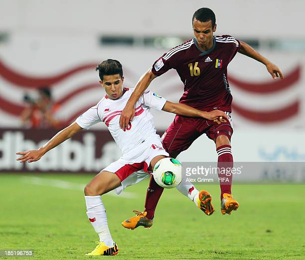 Mohamed Ben Larbi of Tunisia is challenged by Samuel Marquina of Venezuela during the FIFA U17 World Cup UAE 2013 Group D match between Tunisia and...