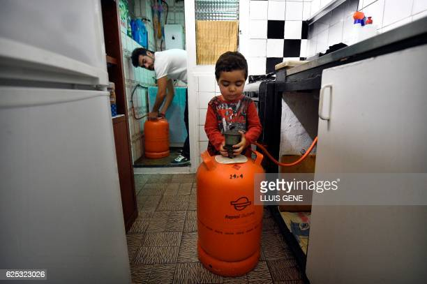Mohamed Chairi and his two year old son Badder change a butane gas bottle during an interview with AFP at their home in Badalona on November 21 2016...