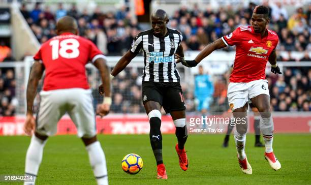 Mohamed Diame of Newcastle United runs with the ball whilst being pursued by Paul Pogba of Manchester United during the Premier League match between...