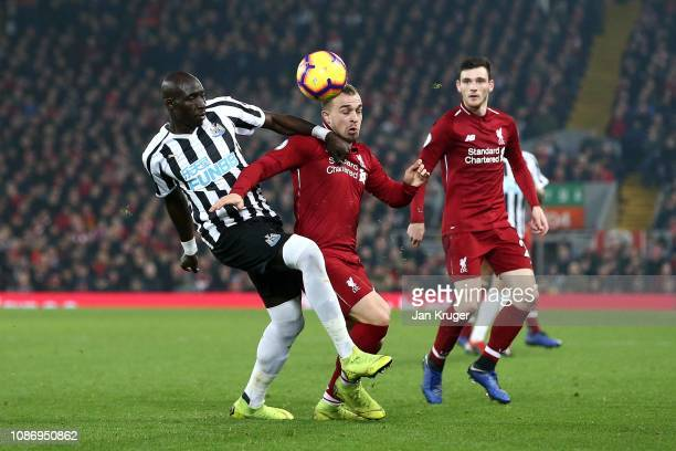Mohamed Diame of Newcastle United tangles with Xherdan Shaqiri of Liverpool during the Premier League match between Liverpool FC and Newcastle United...