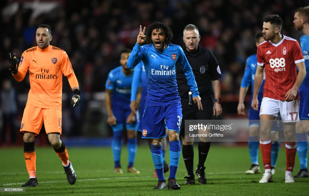 Mohamed Elneny (C) and David Ospina (L) of Arsenal gesture with two fingers watched by referee Jonathan Moss during The Emirates FA Cup Third Round match between Nottingham Forest and Arsenal at City Ground on January 7, 2018 in Nottingham, England.