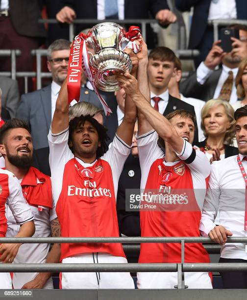 Mohamed Elneny and Nacho Monreal of Arsenal lift the FA Cup Trophy after the match between Arsenal and Chelsea at Wembley Stadium on May 27 2017 in...