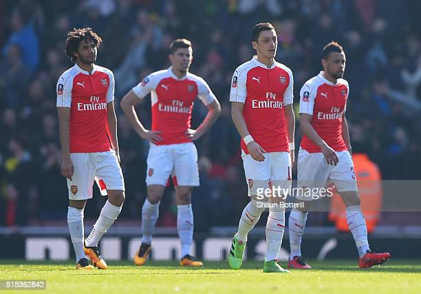 Mohamed Elneny Gabriel Mesut Ozil and Francis Coquelin of Arsenal look dejected as Odion Ighalo of Watford scores their first goal during the...