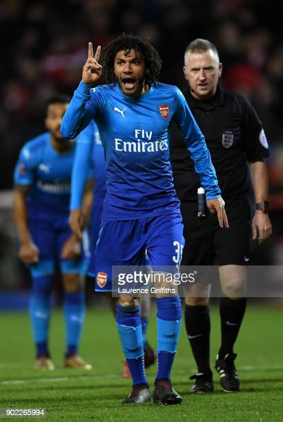 Mohamed Elneny of Arsenal gestures with two fingers watched by referee Jonathan Moss during The Emirates FA Cup Third Round match between Nottingham...